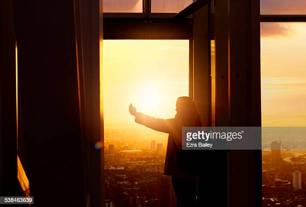 A woman taking a selfie at sunset in the city.