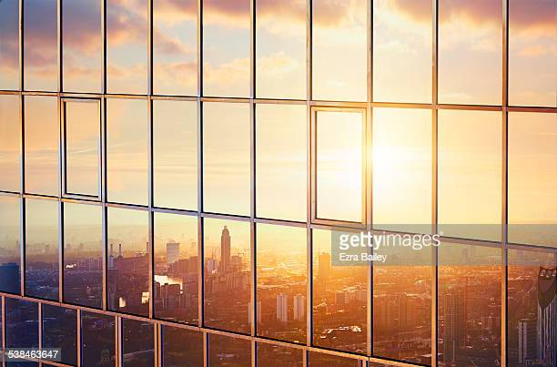 the city at sunrise reflected in a sky scraper. - reflet photos et images de collection