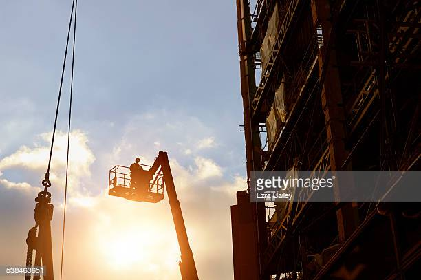 Construction worker silhouetted by a sunset.