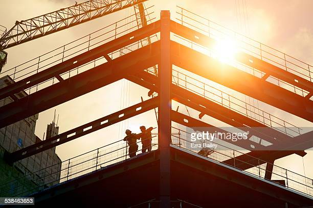 construction workers silhouetted against the sun - construction industry stock pictures, royalty-free photos & images
