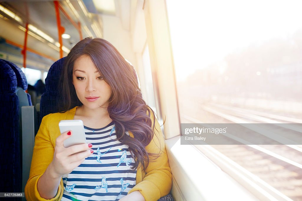Woman on a train looking at her phone. : ストックフォト