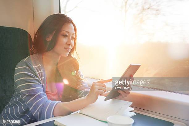 Woman on a train working on a tablet.