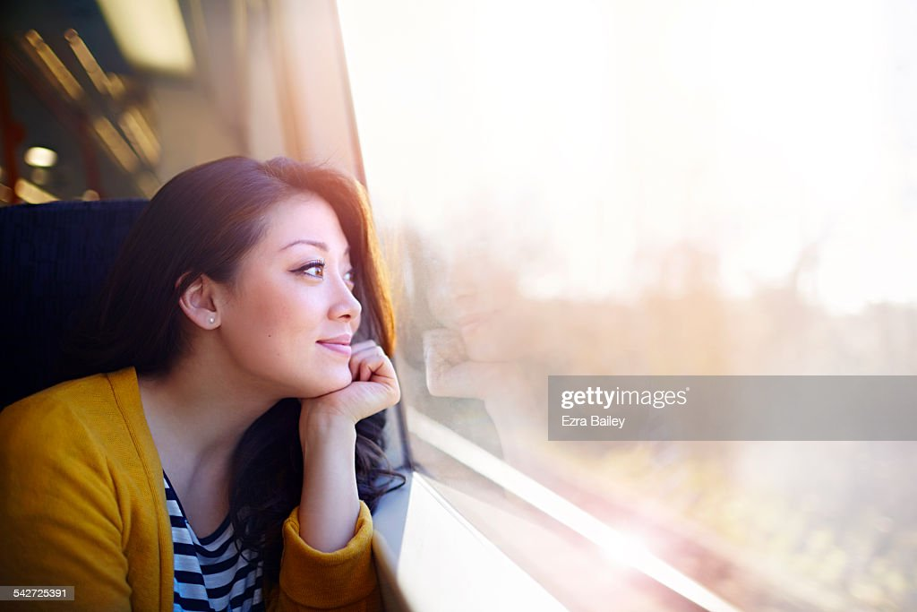 Woman on a train day dreaming out the window. : Stock-Foto