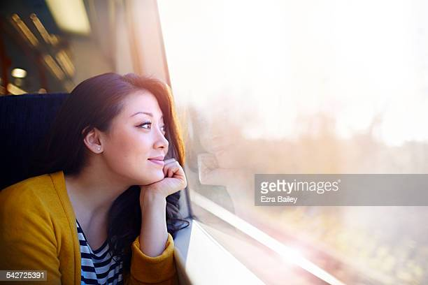 woman on a train day dreaming out the window. - dreaming stock pictures, royalty-free photos & images