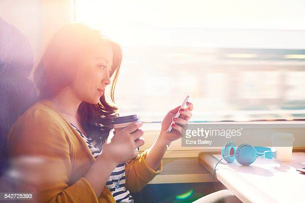 woman on a commuter train looking at her phone. - travel stock pictures, royalty-free photos & images