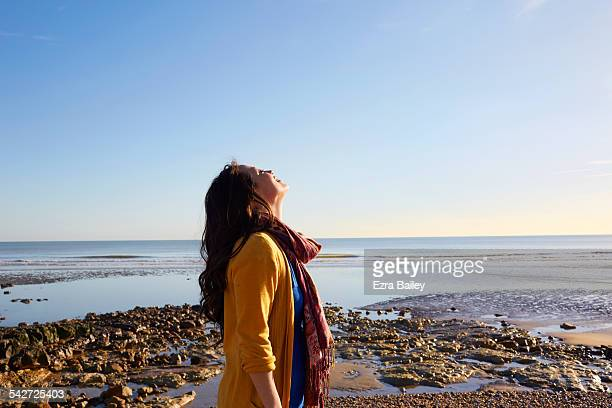 woman on the beach breathing in the fresh air - brown hair stock pictures, royalty-free photos & images