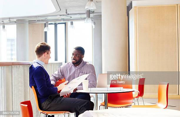 Male colleagues discussing project over coffee