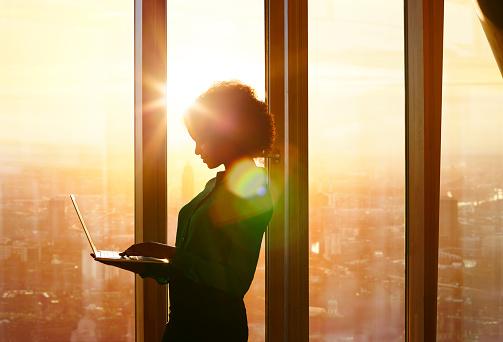Businesswoman on laptop at window in morning sun - gettyimageskorea