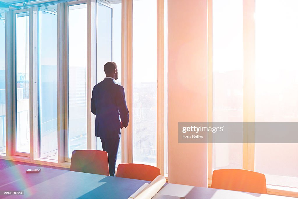Businessman looks out of office window over city : Stock Photo