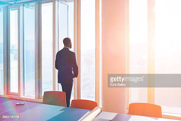 businessman looks out of office window over city - focus concept stock pictures, royalty-free photos & images