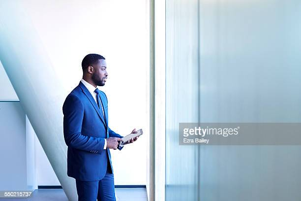 businessman thinking while using tablet - businesswear stock pictures, royalty-free photos & images