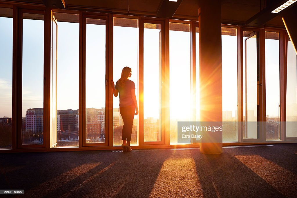 Businesswoman looks across city at sunrise : Stock Photo