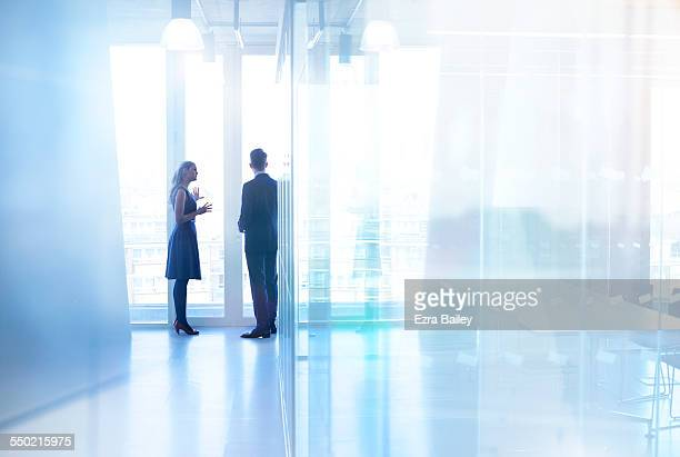 colleagues standing chatting in modern office - leadership stock pictures, royalty-free photos & images
