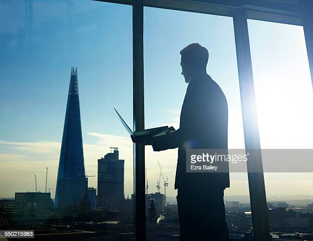 Businessman looking over city holding laptop