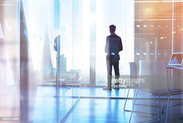 businessman looking out of office over city - vision stock-fotos und bilder