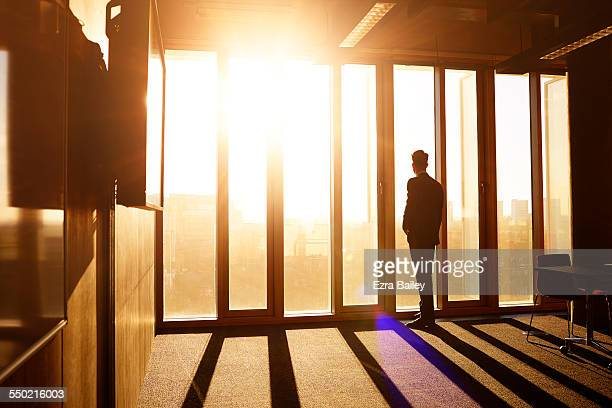 Businessman looks out over city at sunrise