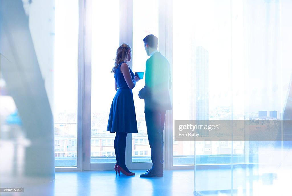 Colleagues with tablet standing at window : Stock Photo