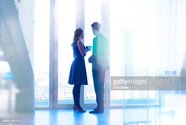 colleagues with tablet standing at window - business meeting stock pictures, royalty-free photos & images