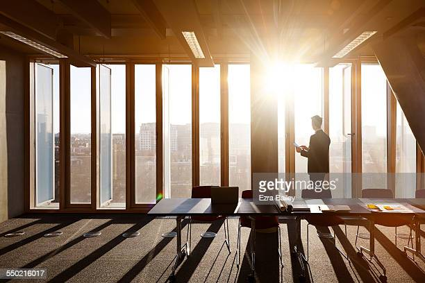 Businessman on tablet looks out across city