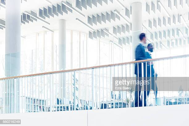 Colleagues walking together through modern office