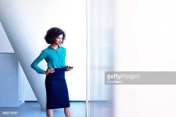 Business woman using phone looking out of window
