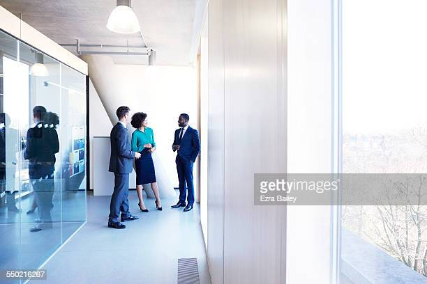 Colleagues chatting in a modern office.