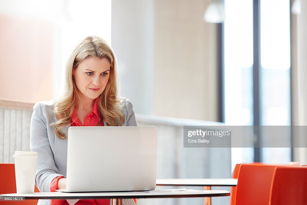 Businesswoman working on laptop in creative office : Stock Photo