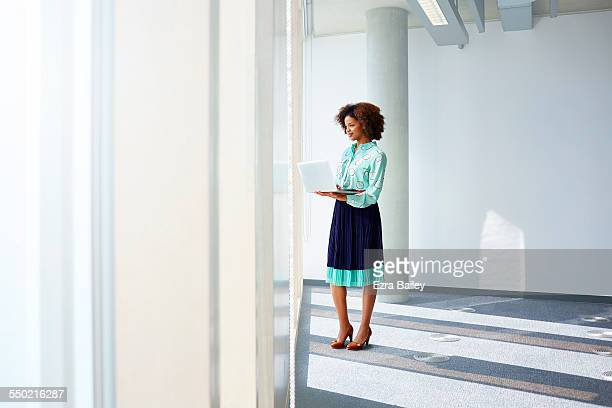 Businesswoman with laptop looking out of window
