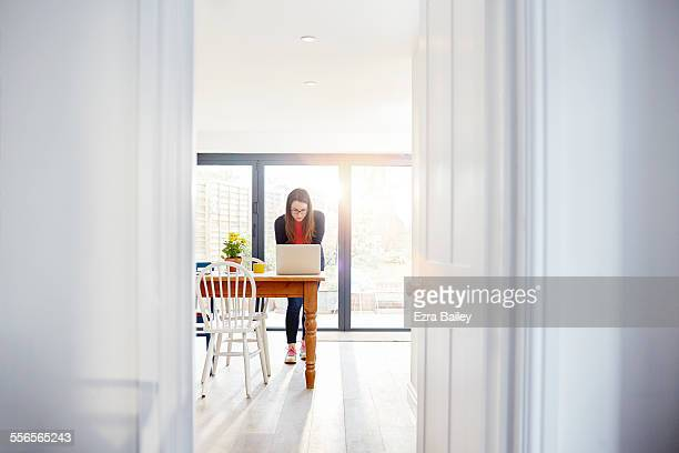 young woman working from home in her kitchen - doorway stock pictures, royalty-free photos & images