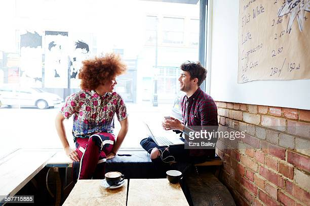 two friends chatting in coffee shop window - two people stock pictures, royalty-free photos & images