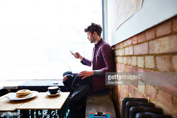 Guy working in coffee shop checks his phone