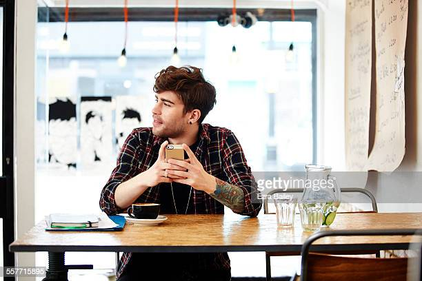 guy with phone relaxing in coffee shop - cool attitude stock pictures, royalty-free photos & images