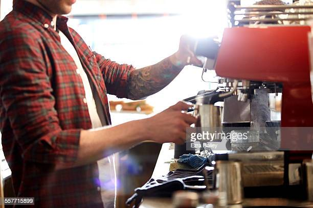 Small business owner heats milk in his coffee shop