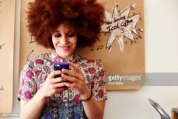 girl smiling as she looks at phone in coffee shop - blouse stock pictures, royalty-free photos & images