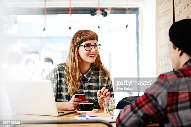 Couple of friends chatting in coffee shop