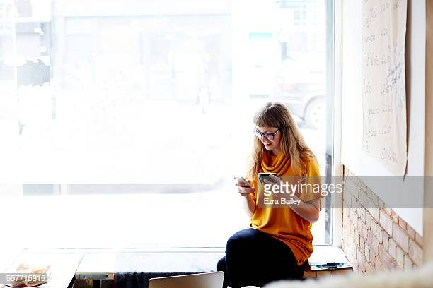 girl sitting in coffee shop window checking phone - one young woman only stock pictures, royalty-free photos & images