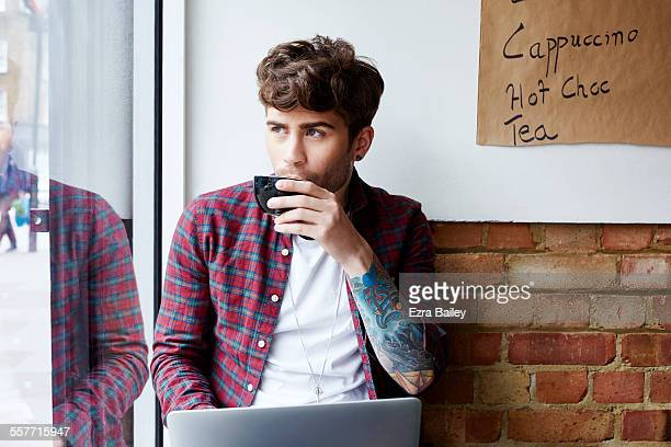 Guy drinking coffee as he looks out of cafe window
