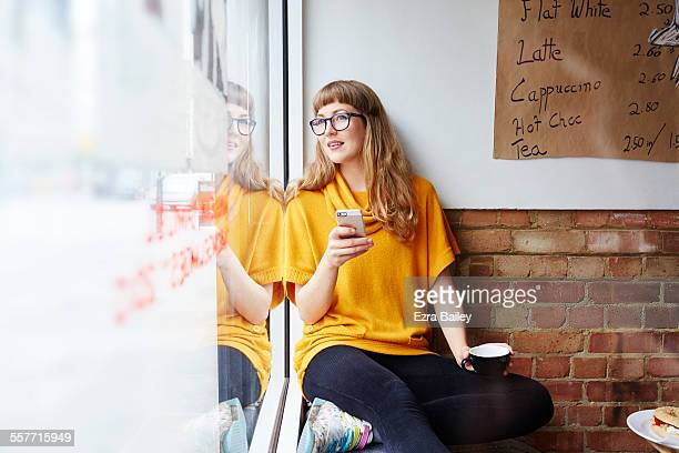 girl with phone looking out of coffee shop window - one young woman only stock pictures, royalty-free photos & images