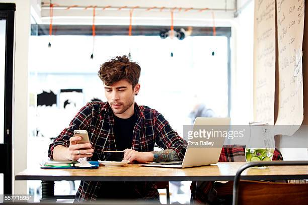 Man checking phone while working in coffee shop