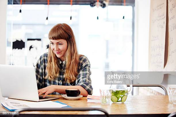 girl working on laptop in trendy coffee shop - using laptop stock pictures, royalty-free photos & images
