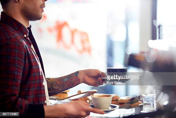 Coffee shop owner serves coffee to customers