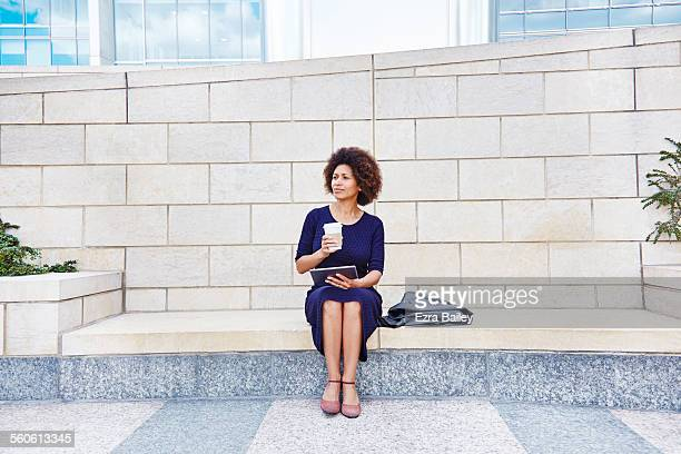 businesswoman thinking as she sits outside - bench stock pictures, royalty-free photos & images