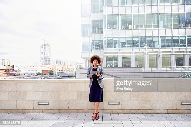 Mixed-race businesswoman using tablet in city