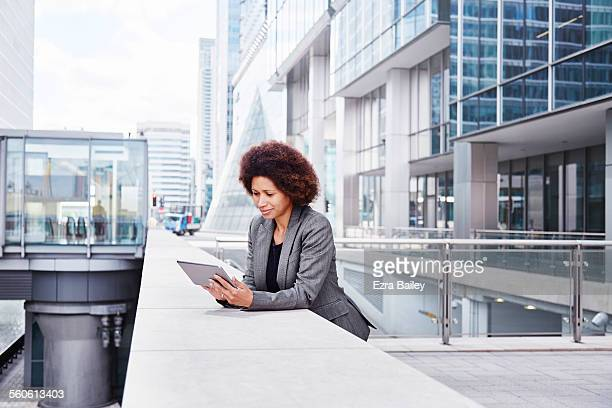 Mixed-race businesswoman on tablet in city