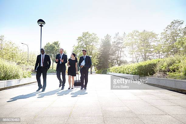 Business men and woman walk and chat together