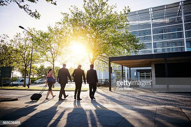Business colleagues walk towards building into sun