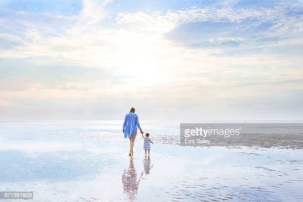 Mother and daughter walking at low tide sunset.