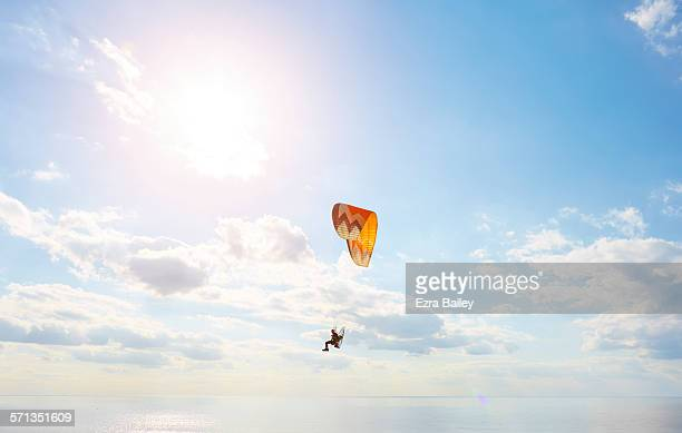 A man using a powered paraglider over the sea