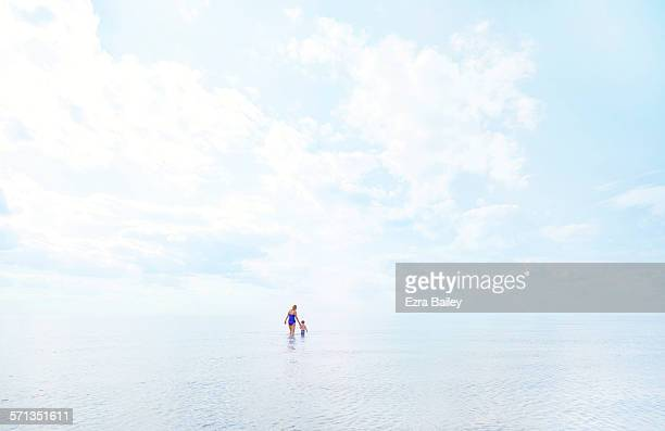 mother and young son wading in the shallow water. - distant stock pictures, royalty-free photos & images