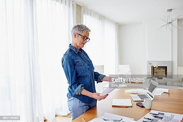 modern businesswoman working from home - solo una donna matura foto e immagini stock